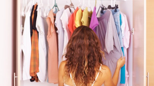 Rear view of a woman going through the clothes in her closet