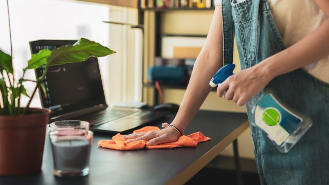 A woman cleans a desk with a laptop on it using a spray bottle with disinfectant and an orange rag.