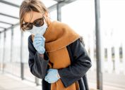 Woman in face mask coughing outdoors