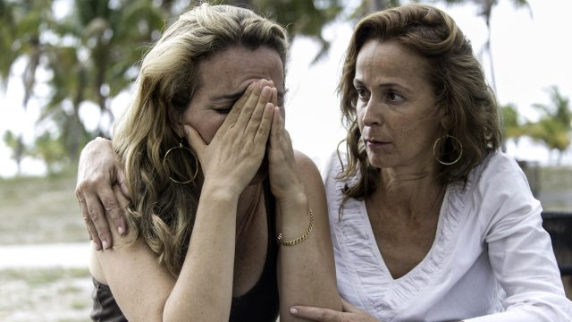 middle aged white woman comforts friend who is dealing with a loss, her head is in her hands