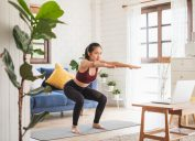 A young woman doing yoga in her living room in front of her laptop.