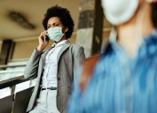 Black woman dressed professionally walks through airport while wearing a mask and talking on the phone