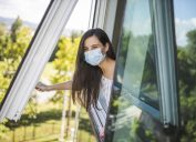 A young woman wearing a face mask while opening a window in her apartment and sticking her head out.