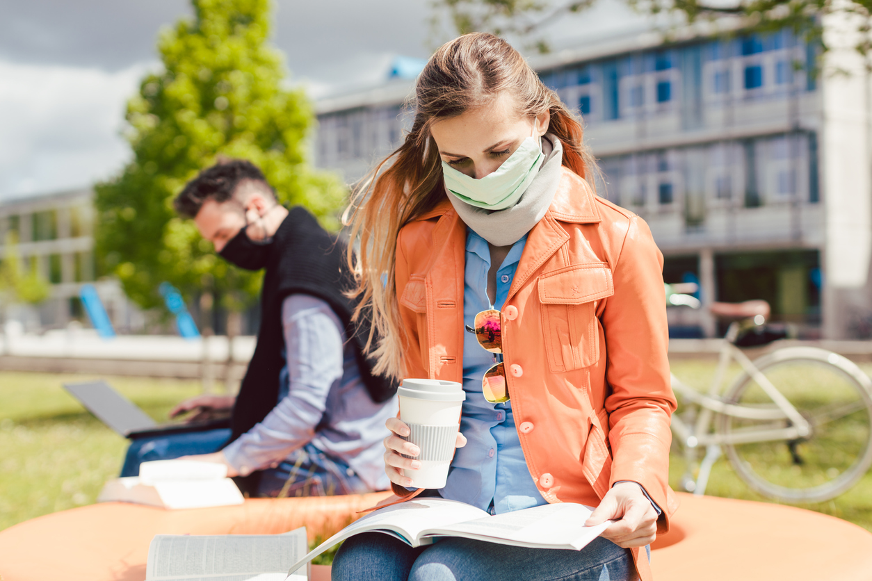A young female student studies her notes while drinking coffee and wearing a face mask on a college campus with a male student in the background.