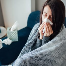 A young woman sitting on the couch wrapped in a blanket and blowing her nose, suffering from flu symptoms.