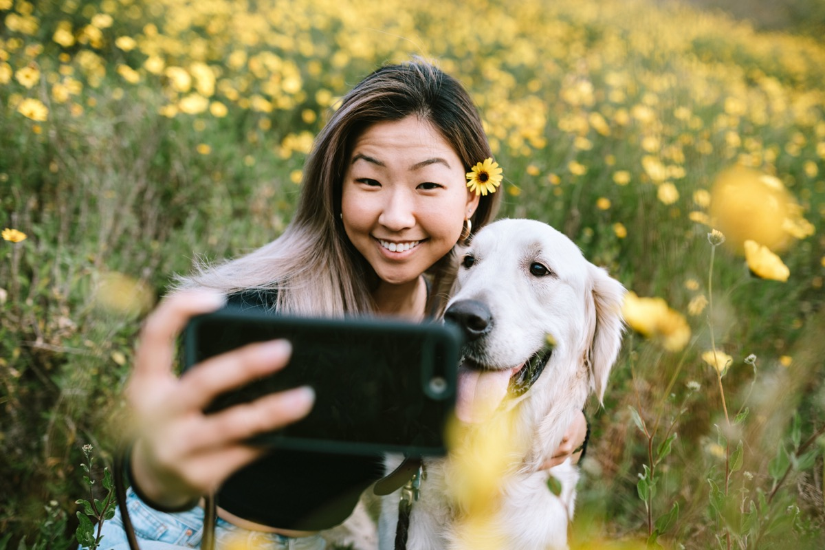 A happy woman enjoys spending time with her Golden Retriever outdoors in a Los Angeles county park in California on a sunny day. She cuddles her beloved pet.
