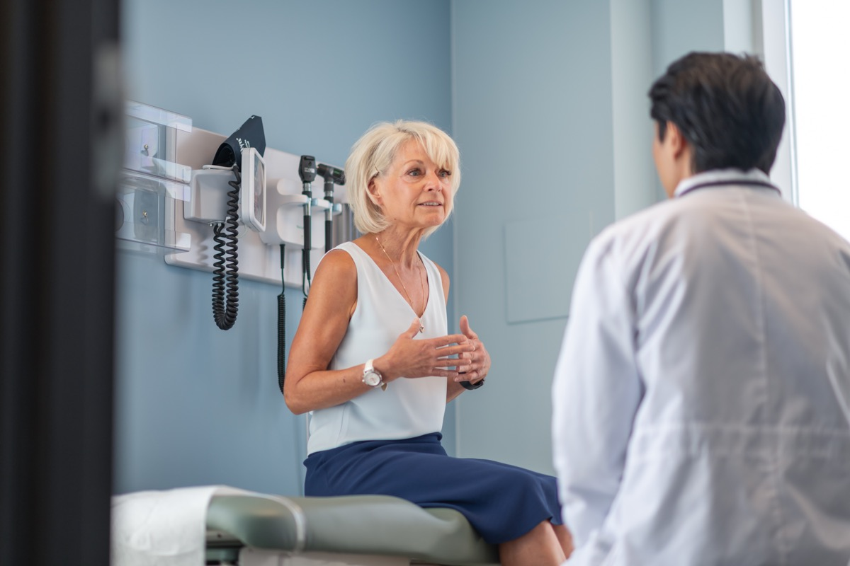 A mature adult woman is at a routine medical appointment. Her healthcare provider is a Korean man. The patient is sitting on an examination table in a clinic. She is explaining her medical history. The kind doctor is listening intently.