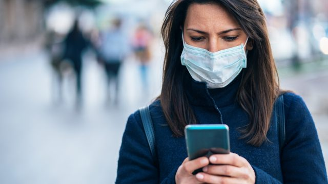 A young woman using her smartphone while wearing a mask due to the coronavirus pandemic.