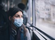 A young woman wearing a face mask riding the bus.