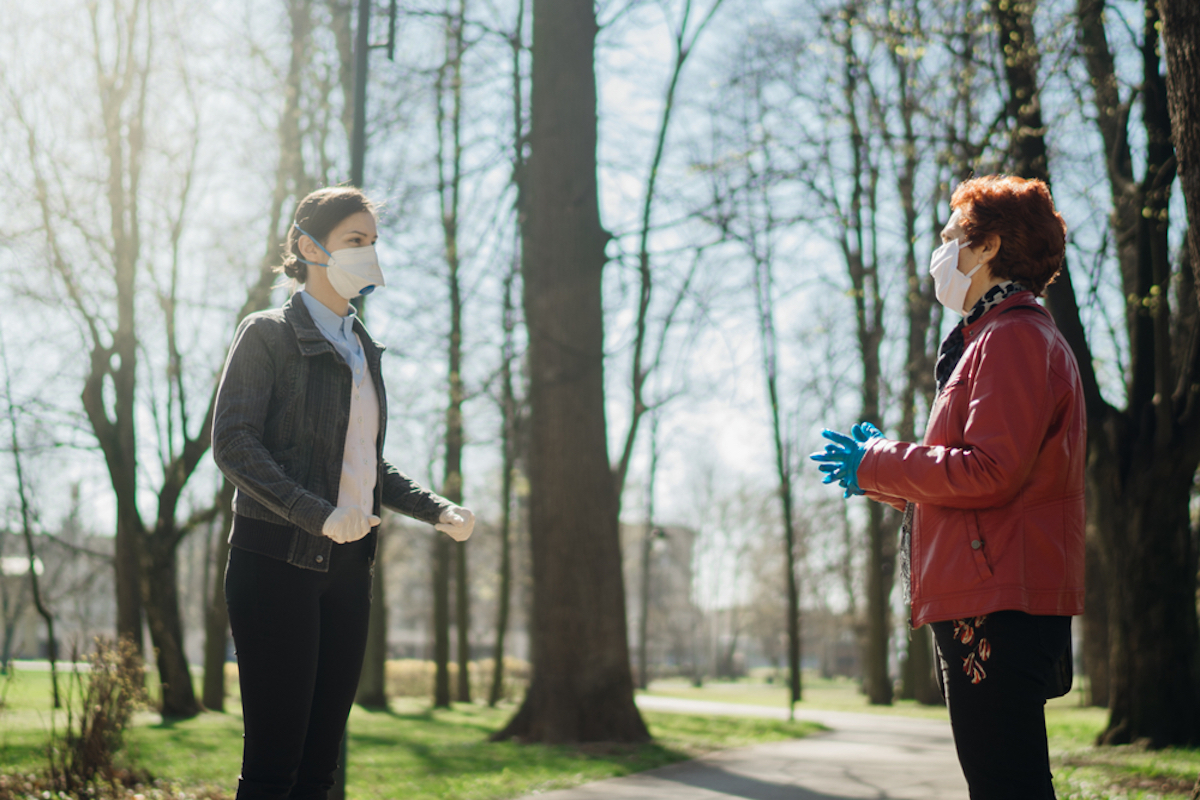 Elderly woman with protective face mask/gloves talking with a friend outside