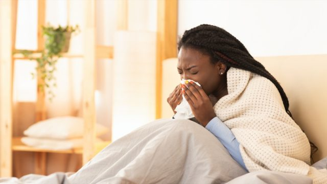 young black woman under blanket sneezing or blowing nose while sick