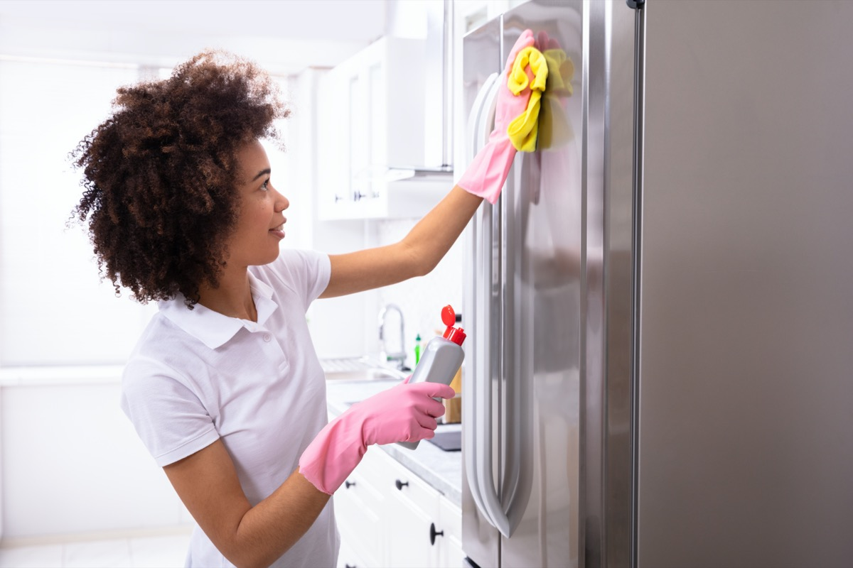 Woman cleaning fridge with gloves