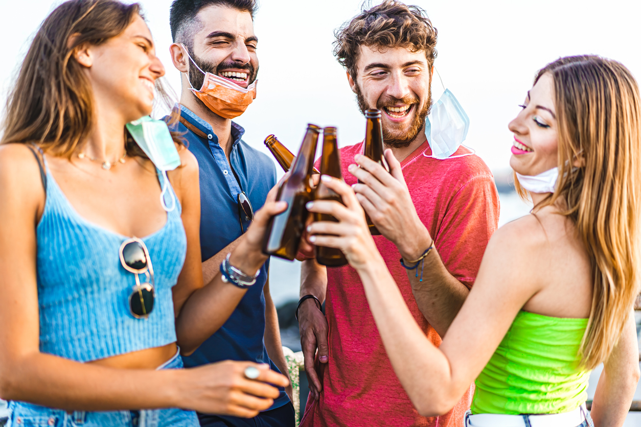 A group of four young men and women cheers beer bottles together with their face masks hanging off, making it easier to spread coronavirus