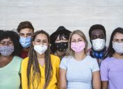 A group of multiethnic young people wearing different face masks and smiling.