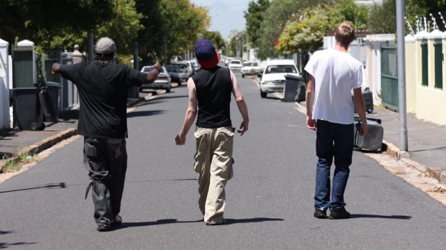 Shot of three young men walking down a suburban street