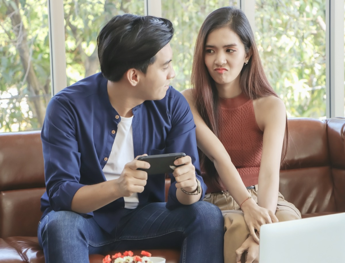 Young man playing on phone, young woman sitting next to him upset