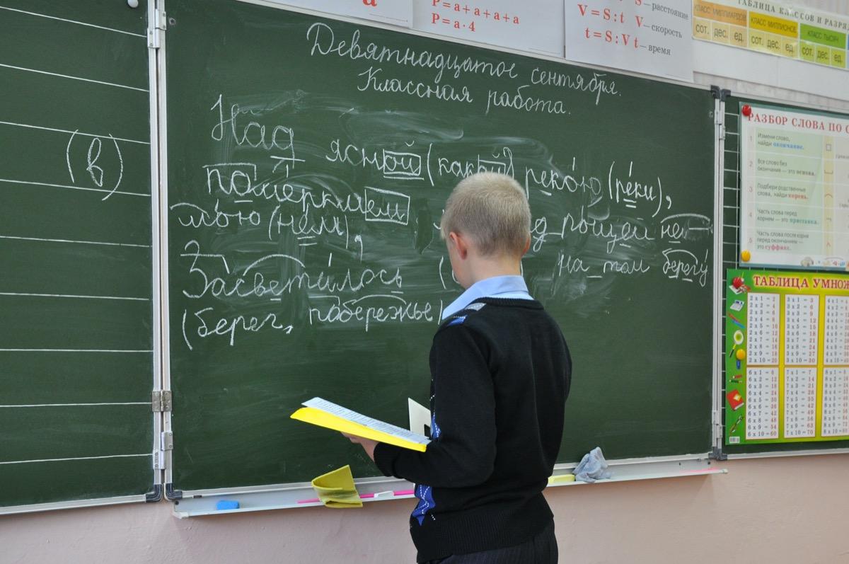 Little boy writing Russian on blackboard