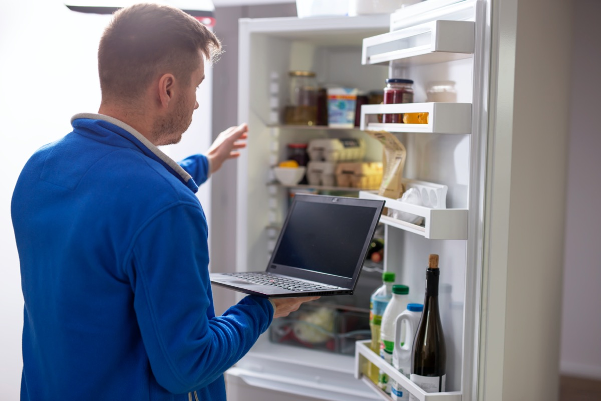 Man holding laptop and reaching into refrigerator