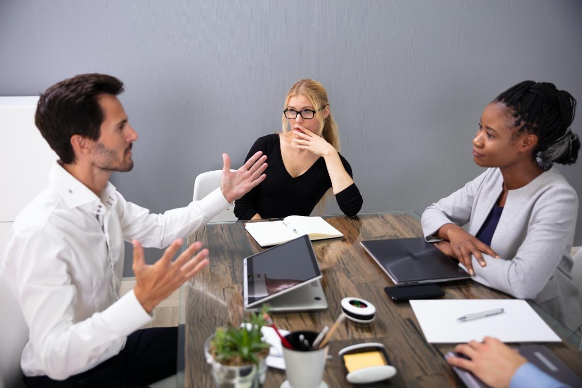 Man explaining something to two women in business meeting