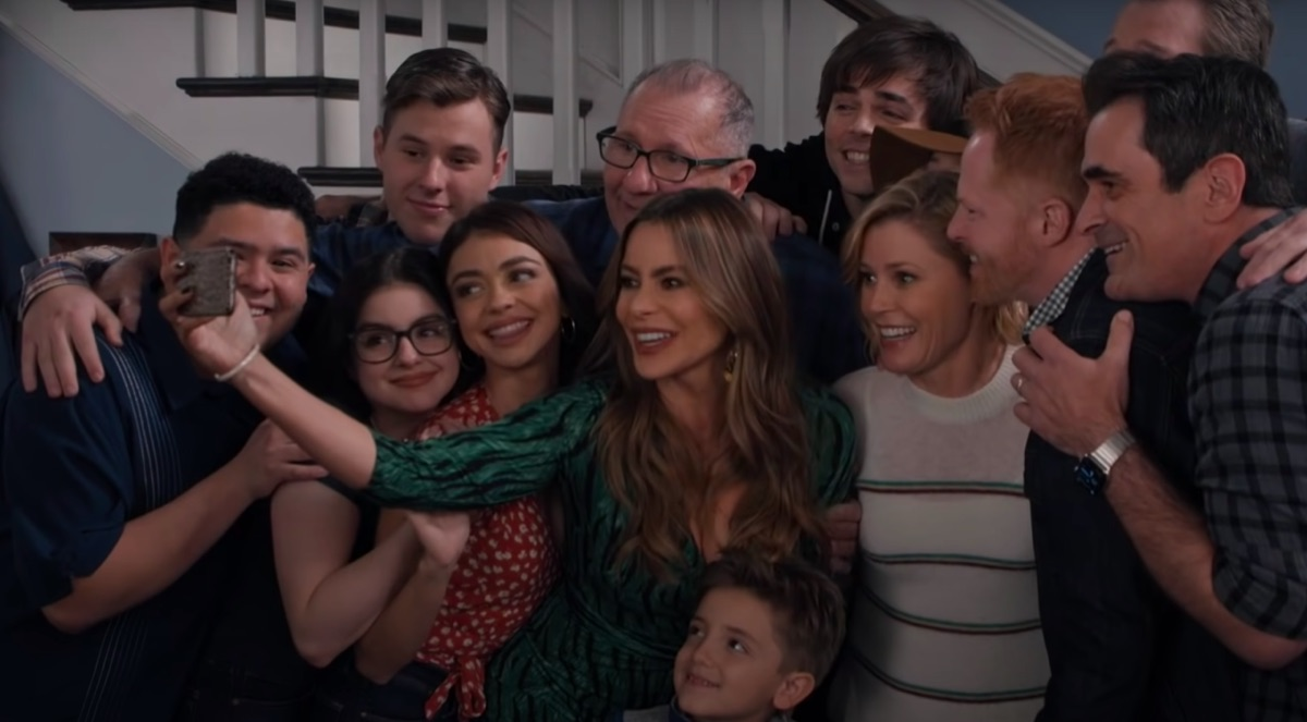 the cast of Modern Family taking a photo together in their final episode