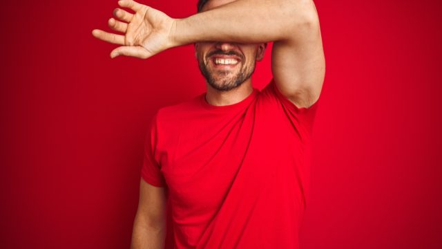 White man laughing and covering eyes