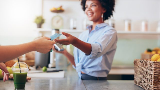 Cropped shot of female employee taking payment from customer, focus on female hands giving credit card for juice bar payment.