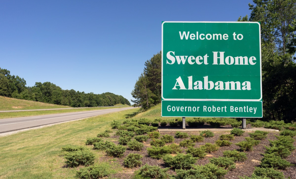 """a green """"Welcome to Sweet Home Alabama"""" sign in front of green plants and off a highway"""
