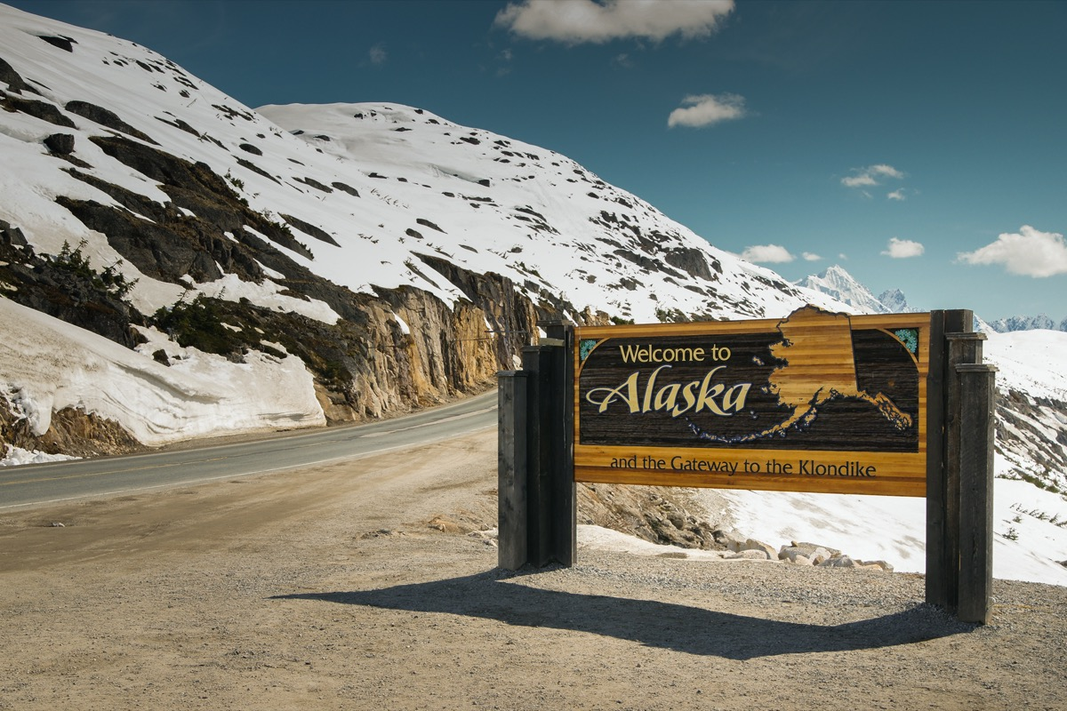 """a wooden """"Welcome to Alaska"""" in front of white mountains and off of a highway"""