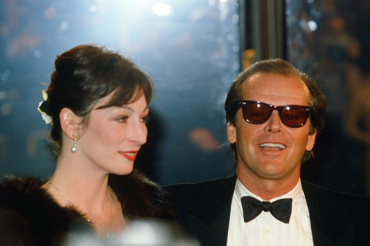 Anjelica Huston wears a black coat and Jack Nicholson wears a black suit at the American Film Institute Gala Tribute to John Huston in 1983