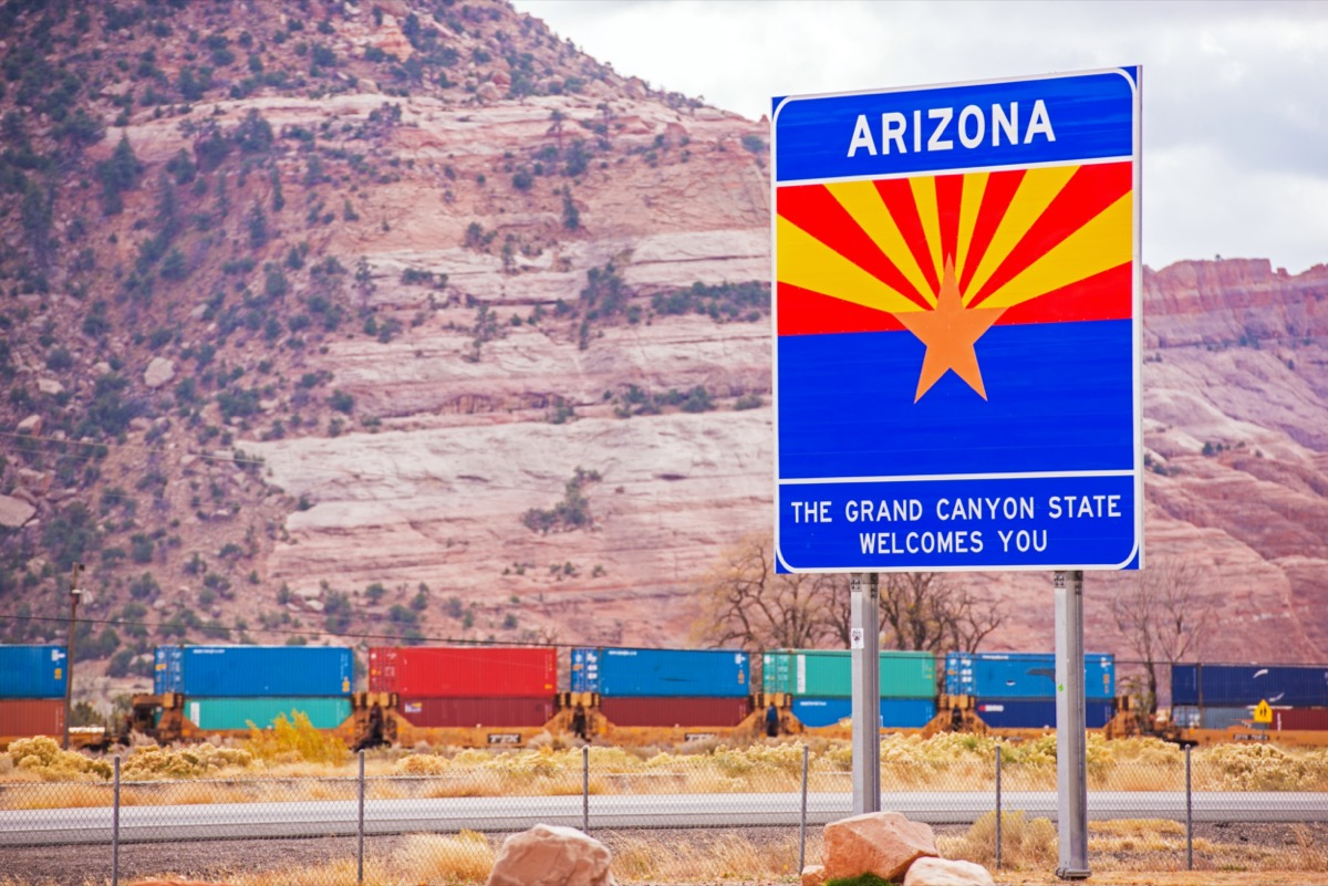 """a blue """"Arizona"""" sign off of the highway and in front of the Grand Canyon"""