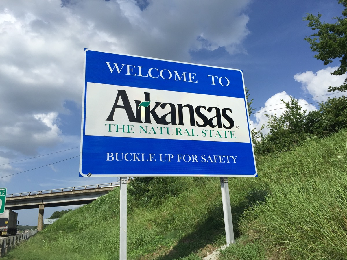 """a blue """"Welcome to Arkansas"""" sign within green grass and off of a highway"""