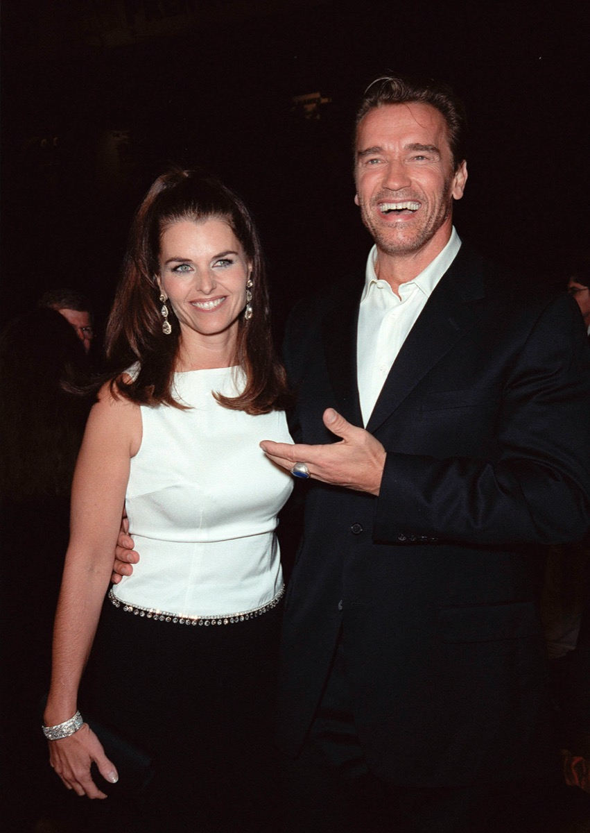 Arnold Schwarzenegger wears a black suit and Maria Shriver wears a white top at the premiere of 'End Days' in 1999