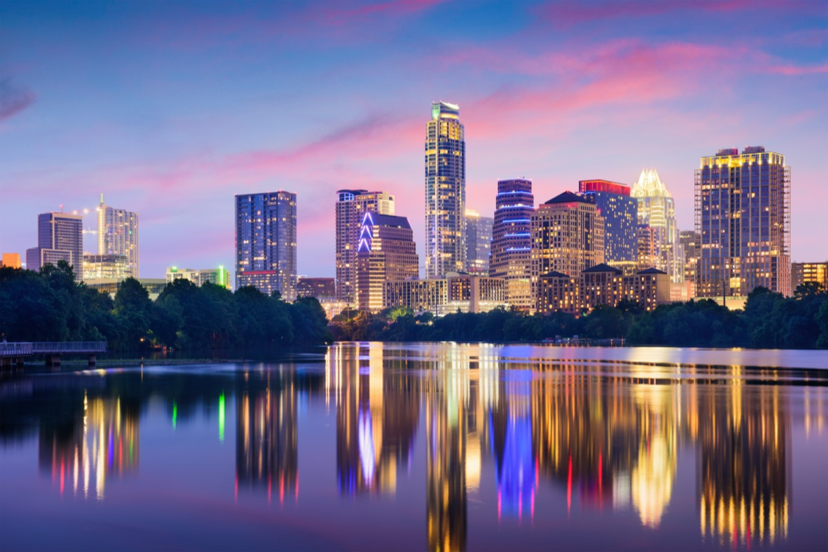 city skyline on the Colorado River in Austin, Texas at dusk