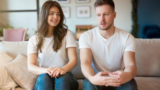 Awkward couple sitting on couch avoiding intimacy