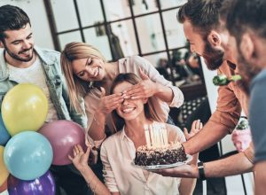 group of friends surprises a woman with a birthday cake