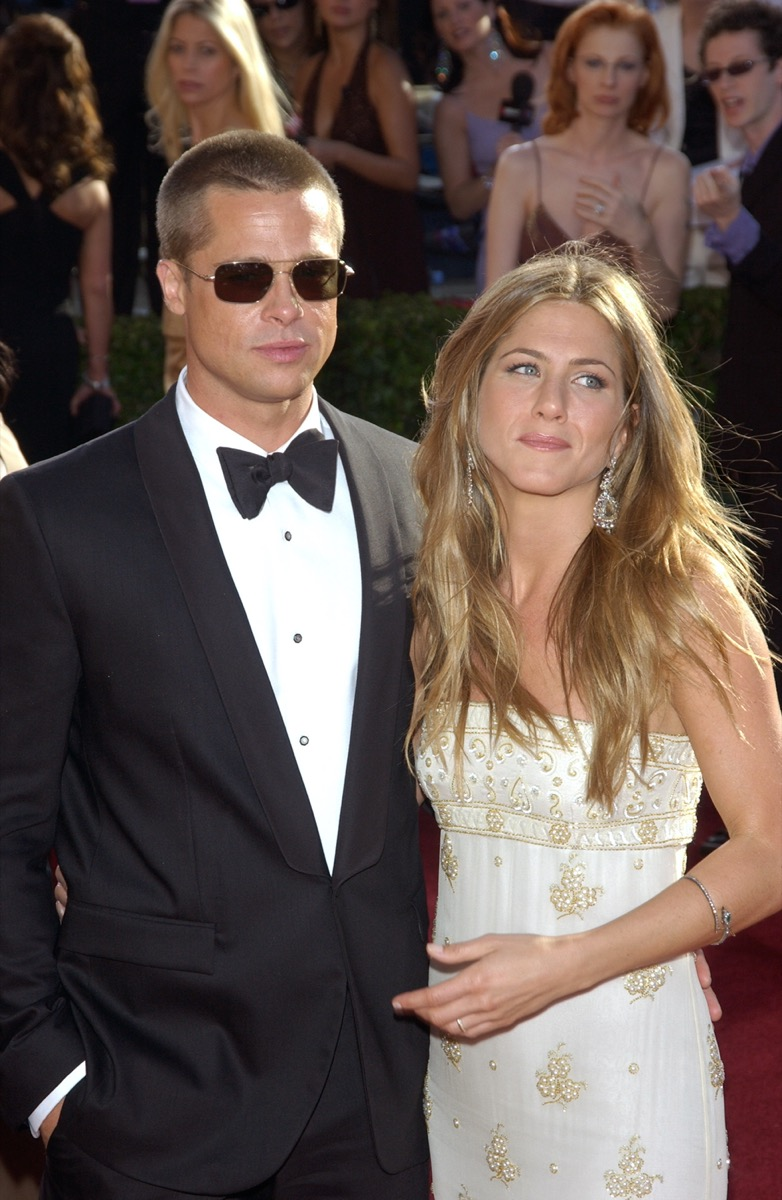 Jennifer Aniston wears a white dress and Brad Pitt wears a black suit on the red carpet at the Emmy Awards in 2004