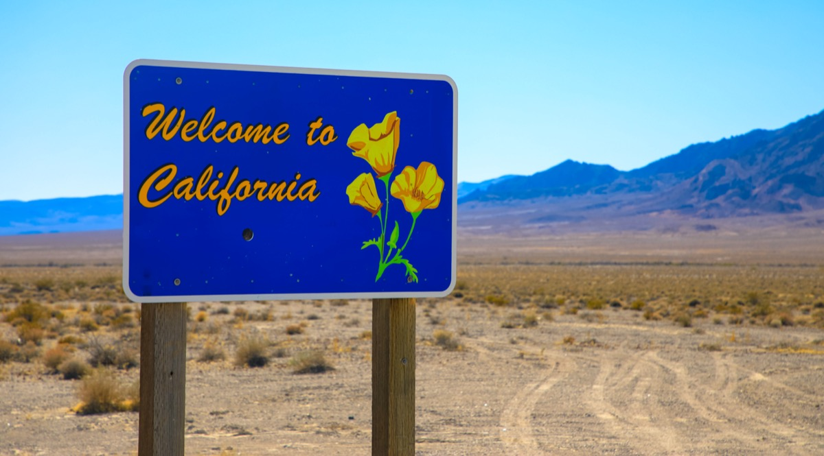 """a blue """"Welcome to California"""" sign on a dirt road"""