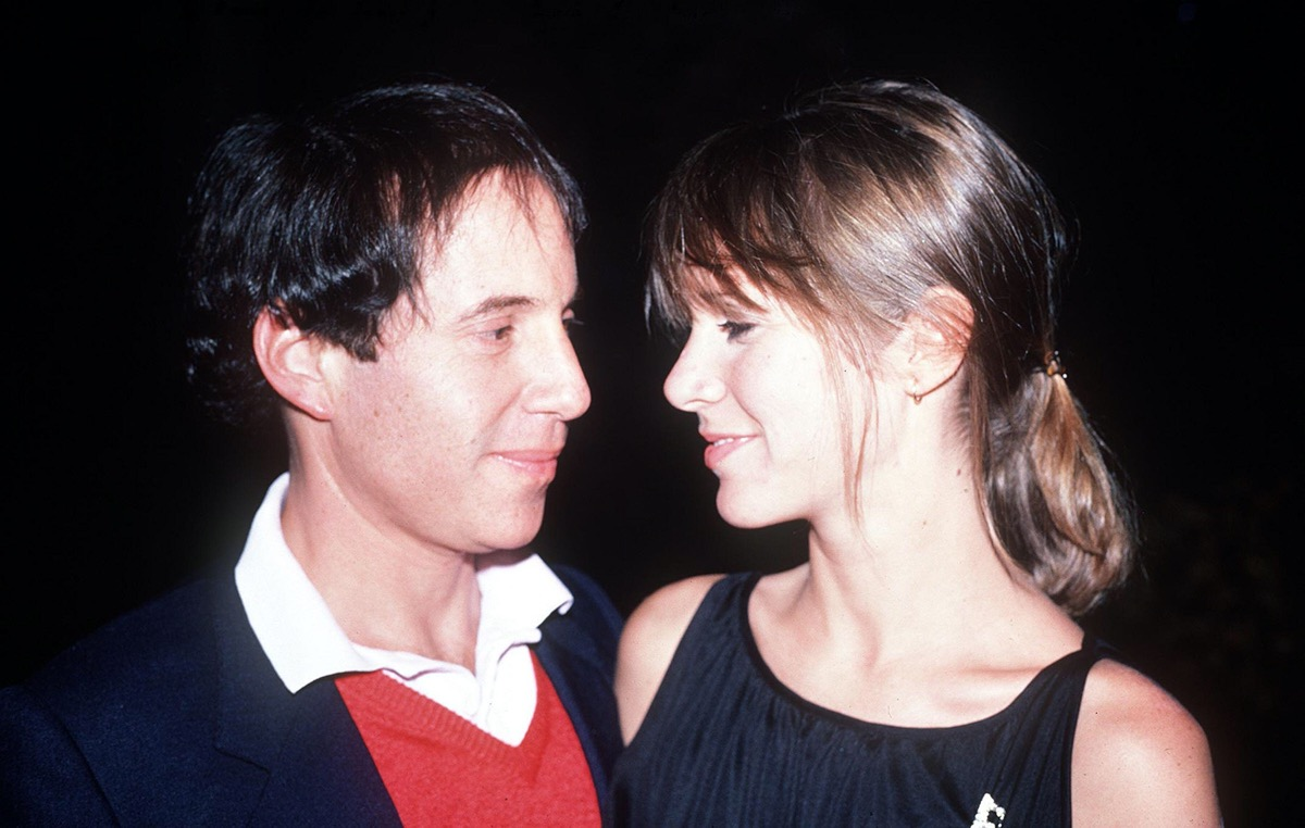 Carrier Fisher wears a black dress and Paul Simon wears a red sweater and black jacket in 1982