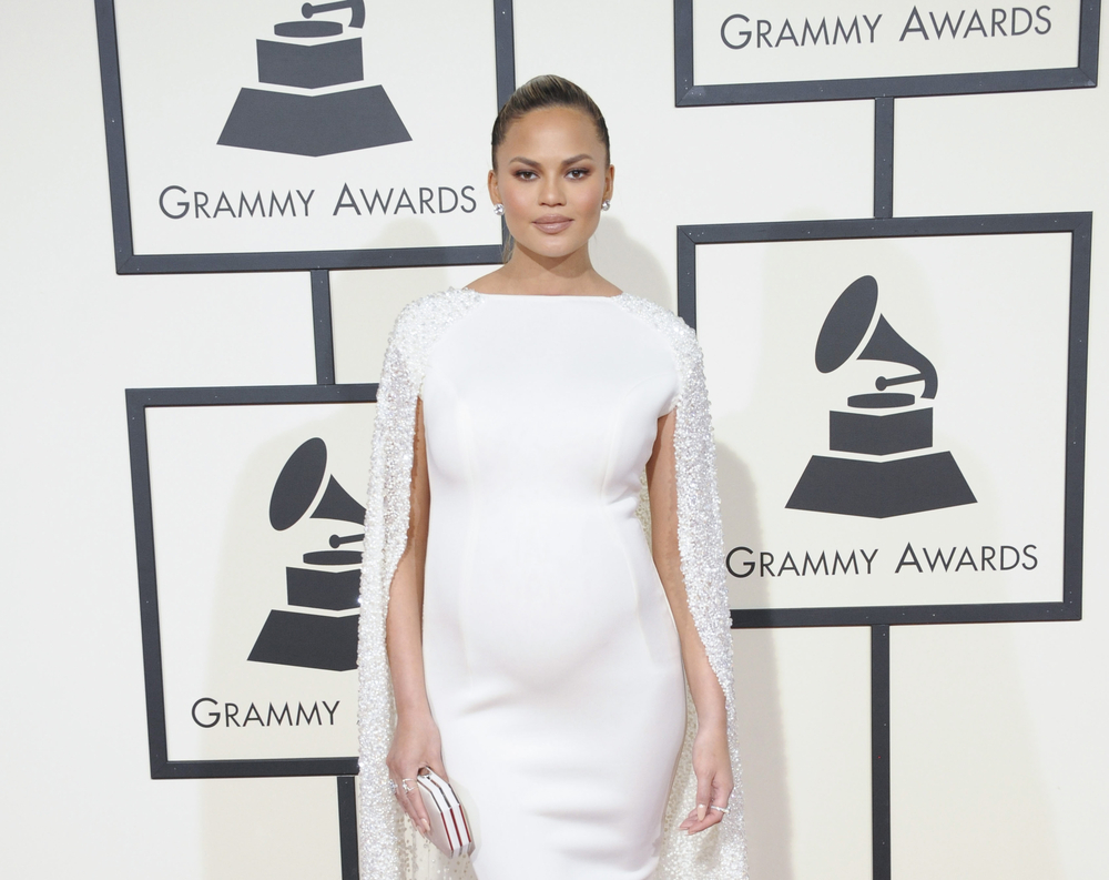 Chrissy Teigen at the Grammys red carpet wearing a white dress