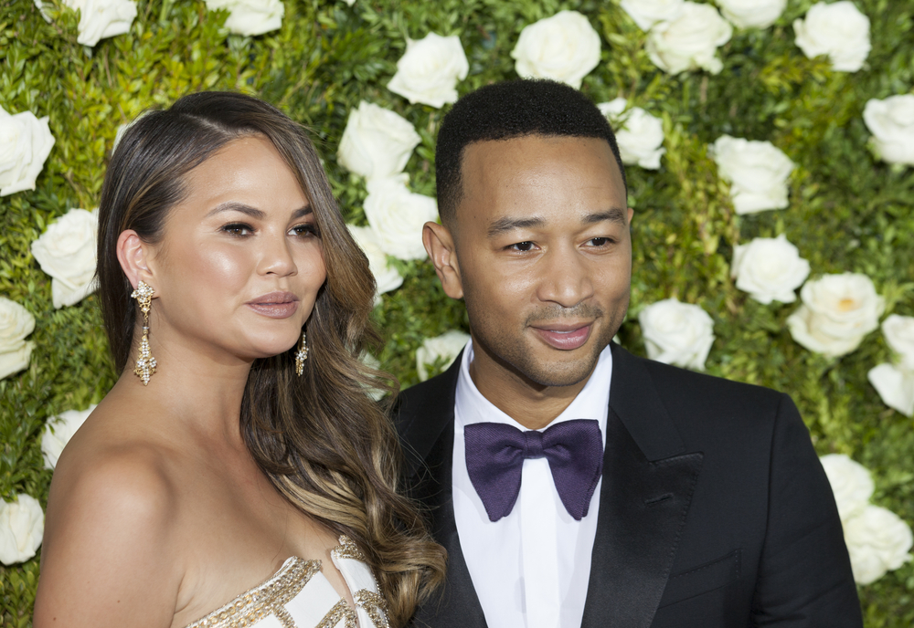 Chrissy Teigen and John Legend standing in front of a green wall