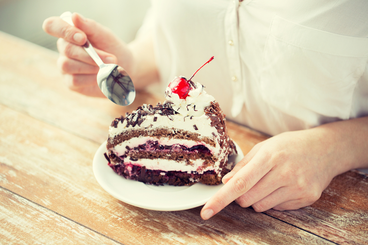 close up of woman eating chocolate cherry cake with spoon and sitting at wooden table