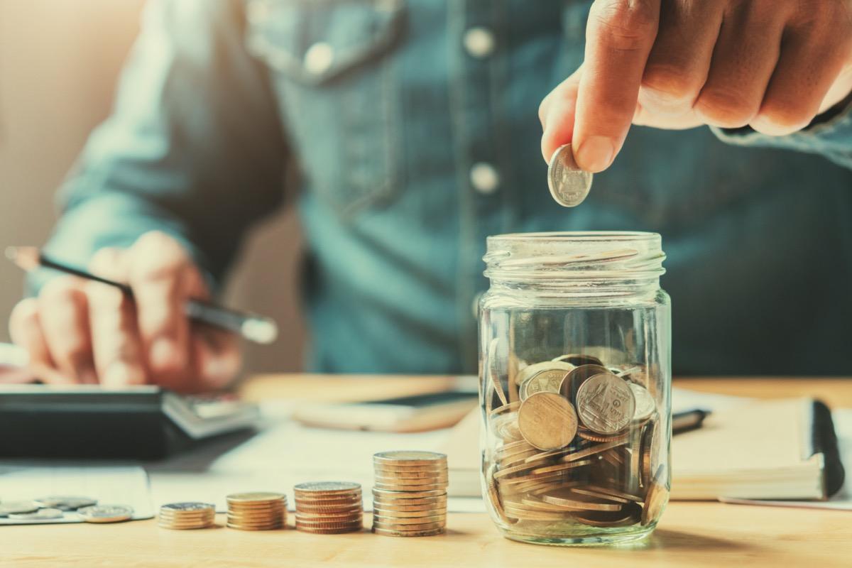 man putting coins in a jar
