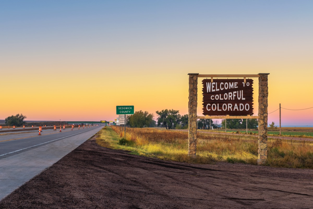 """a wooden """"Welcome to Colorful Colorado"""" sign off of the highway at sunset"""