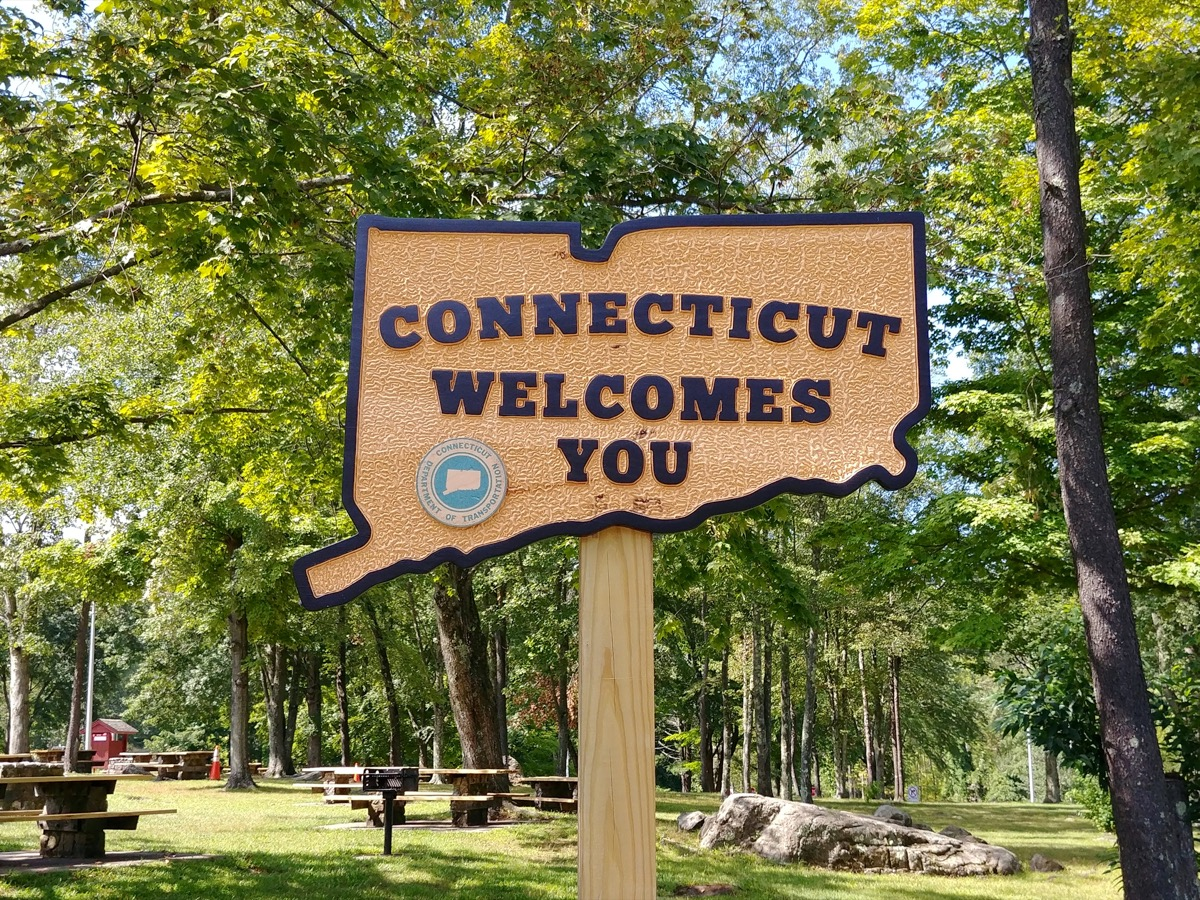 """a wooden sign that says """"Connecticut Welcomes You"""" in a park"""