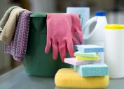 Bucket, sponges, gloves, disinfectant wipes and Protective face masks on desk in preparation to clean offices and furnishings.