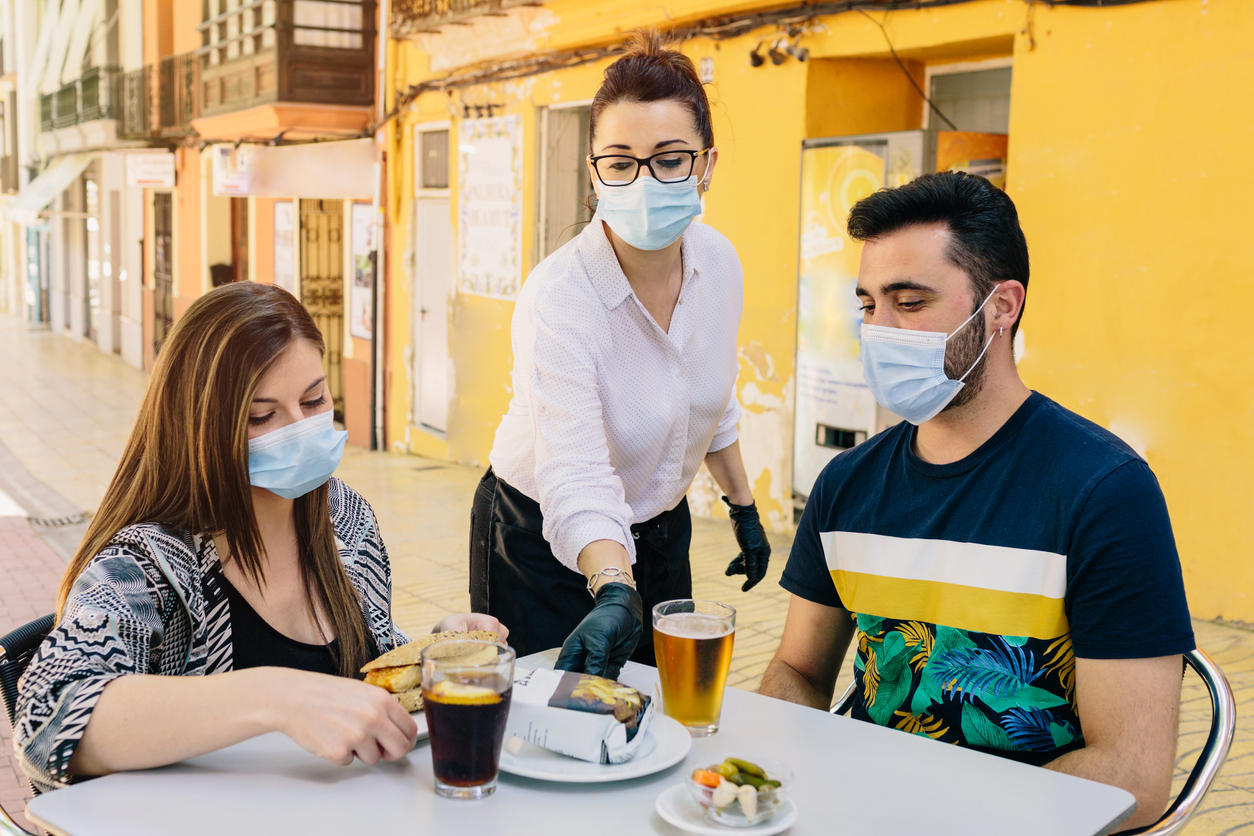 A male and female couple are waited on by a female server at an outdoor table while all wearing face masks