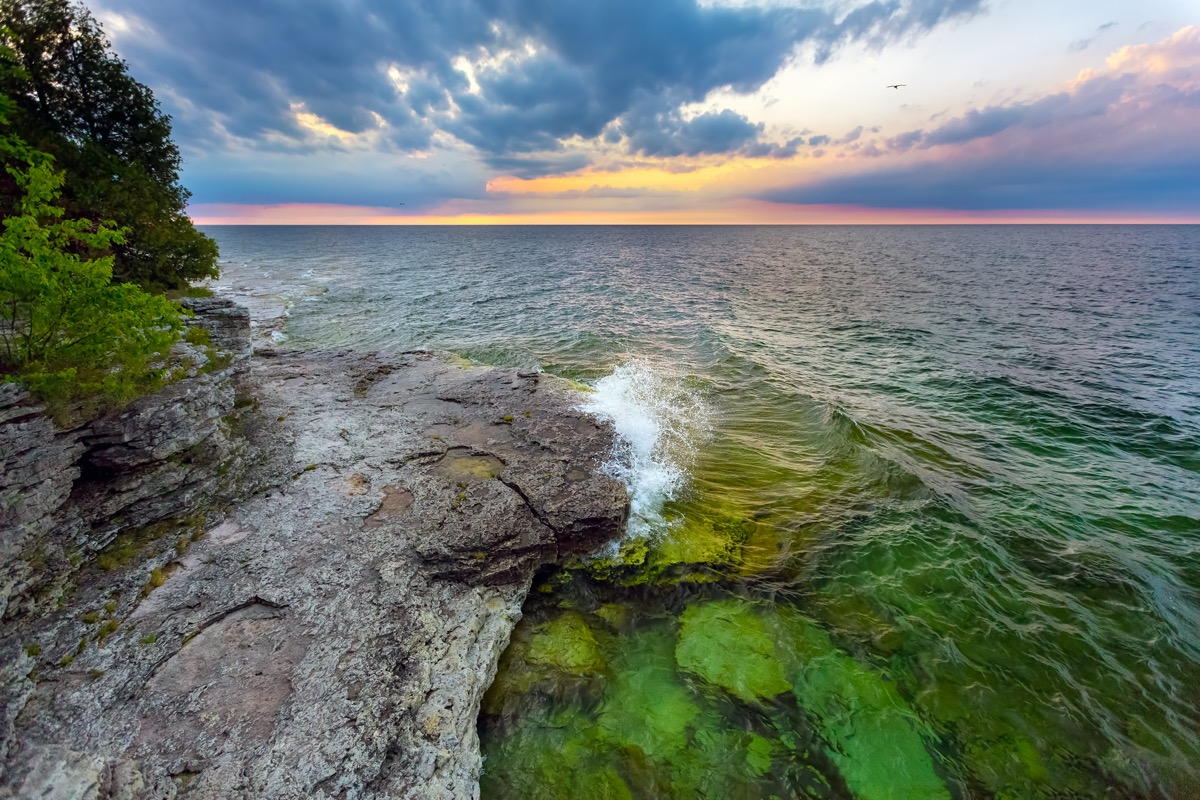 waves breaking next to trees and rocks on the coast of Wisconsin's Cave Point at dawn