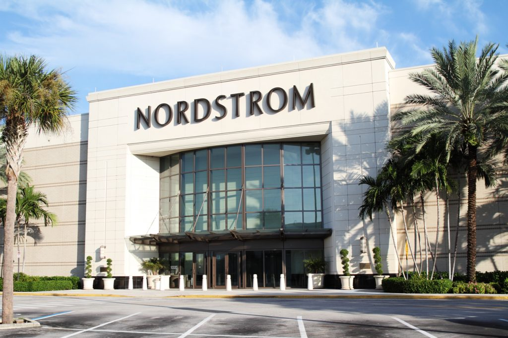 The exterior of a Nordstrom store whose entrance is flanked by palm trees
