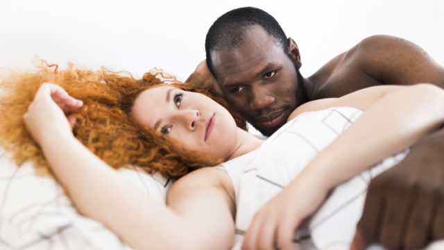 white woman with red hair and black man look frustrated while laying down together