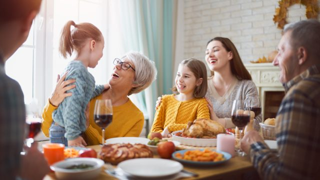 A family celebrates Thanksgiving at the dinner table while a mother and daughter watch on as a grandmother hugs her grandaughter